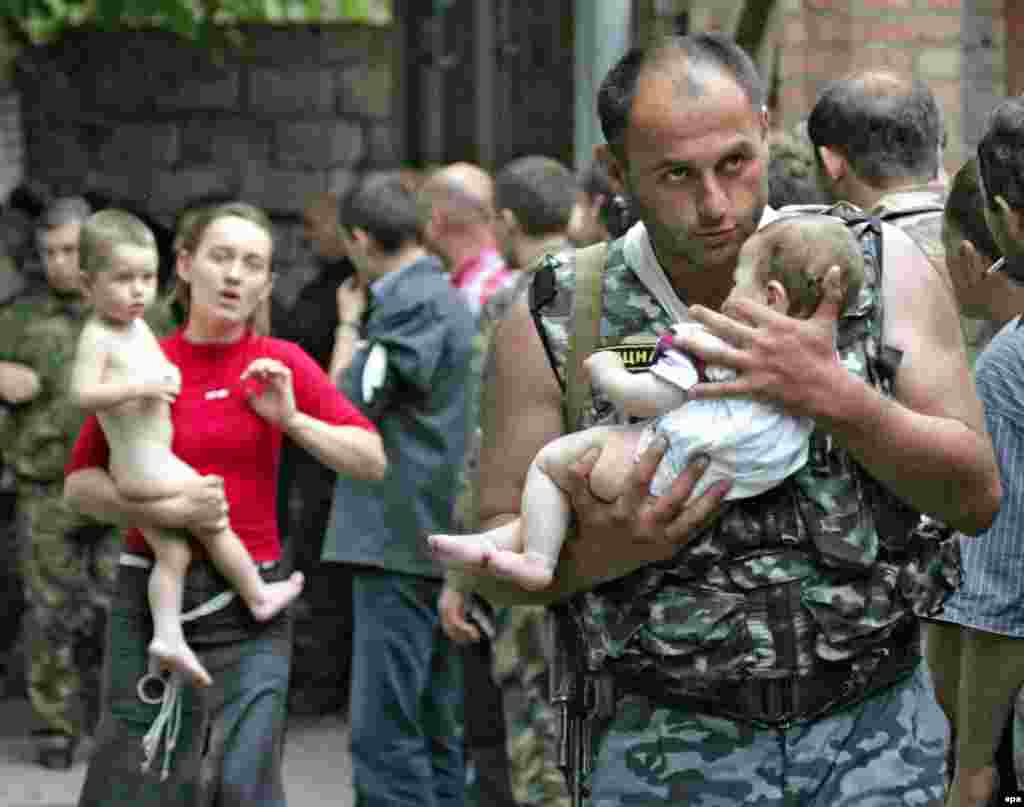 A soldier carries a baby after the release of 26 women and children on the second day of the crisis. Officials say the hostage takers started the massacre by setting off a bomb inside the school, but many in Beslan say the soldiers provoked the battle by firing a rocket-propelled grenade at the school, causing the roof to collapse and sparking a fierce blaze.