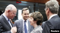 EU foreign policy chief Catherine Ashton (second from right) talks with Dutch Foreign Minister Uri Rosenthal (left), Polish Foreign Minister Radoslaw Sikorski (second from left), and German Foreign Minister Guido Westerwelle in Brussels on March 21.
