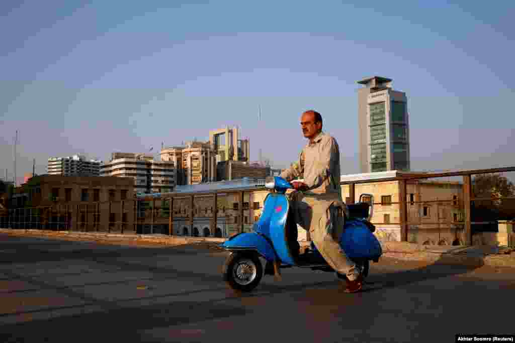 "Journalist Arif Balouch, 48, poses for a photograph with his 1980 Vespa in Karachi. ""For me, a Vespa scooter is like a family tradition. My father used to ride this and I myself find this very good as it has two separate comfortable seats which is uncommon; it has a compartment to keep things, which is also uncommon; and for safety it guards your knees during accidents. I would say it's the BMW of scooters,"" Balouch told Reuters."