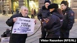 Участник одиночного пикета против войны на Украине на Невском проспекте в Санкт-Петербурге под взглядами полицейских