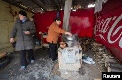 Женщины готовят еду на печи у их дома в селе Спартак Донецкой области. 21 октября 2014 года.