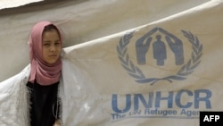 A girl looks out from a rip in a UNHCR tent at the Chukook camp for the internally displaced in northwest Baghdad. (file photo)