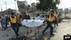 Rescue workers move the body of a victim at the site of an explosion in the eastern Pakistani city of Lahore on July 24.