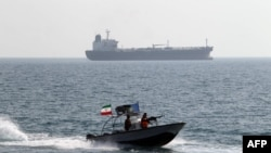 Iranian Revolutionary Guards drive a speedboat in front of an oil tanker during a ceremony to commemorate the 24th anniversary of the downing of Iran Air flight 655 by the US navy, at the port of Bandar Abbas on July 2, 2012.