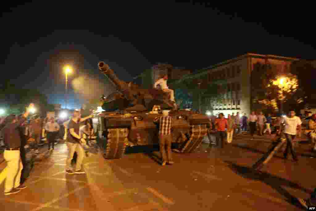 People try to take over a tank in Ankara. In an address to Turkish television, Erdogan had urged people to take to the streets.
