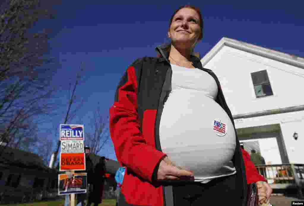 A pregnant woman shows off the voting sticker on her belly outside the old Town Hall in Bristol, New Hampshire.