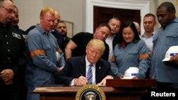 Президент Дональд Трамп болот менен алюминийге бажы салыгын киргизүү чечимине кол коюп жатат. Вашингтон, 8-март, 2018-жыл.