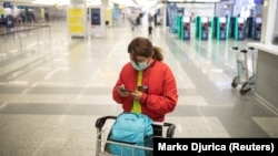 A passenger checks her mobile phone as Serbia halts all commercial flights from Belgrade's airport to prevent the spread of coronavirus on March 19.