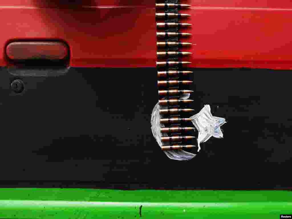 An ammunition belt hangs over a car door painted in the colors of the rebel Kingdom of Libya flag near Brega in eastern Libya on March 30. Photo by Finbarr O'Reilly for Reuters