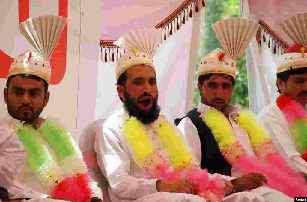 A groom yawns as he sits with others during a mass wedding ceremony in Peshawar, Pakistan. (Reuters/Fayaz Aziz)