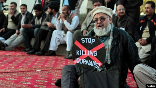 Pakistan -- A journalist holds a placard while taking part in a demonstration in front of the Parliament building in Islamabad, 28Jan2013