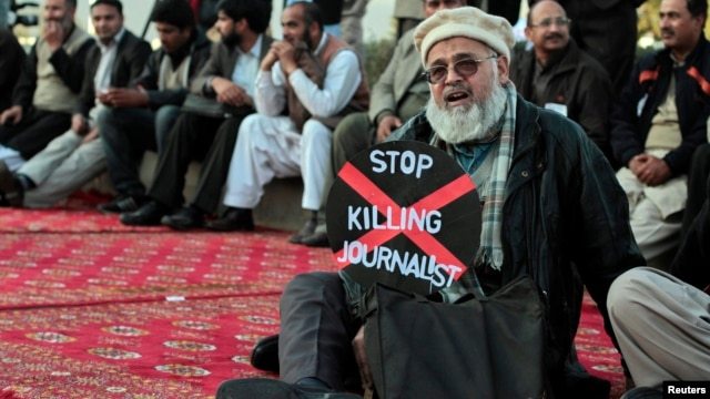 A journalist holds a placard while taking part in a demonstration in front of the Pakistani parliament building in Islamabad on January 28 to highlight the plight of his colleagues.