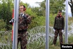 Militari unguri înălțînd un gard împotriva refugiaților la granița cu Croația
