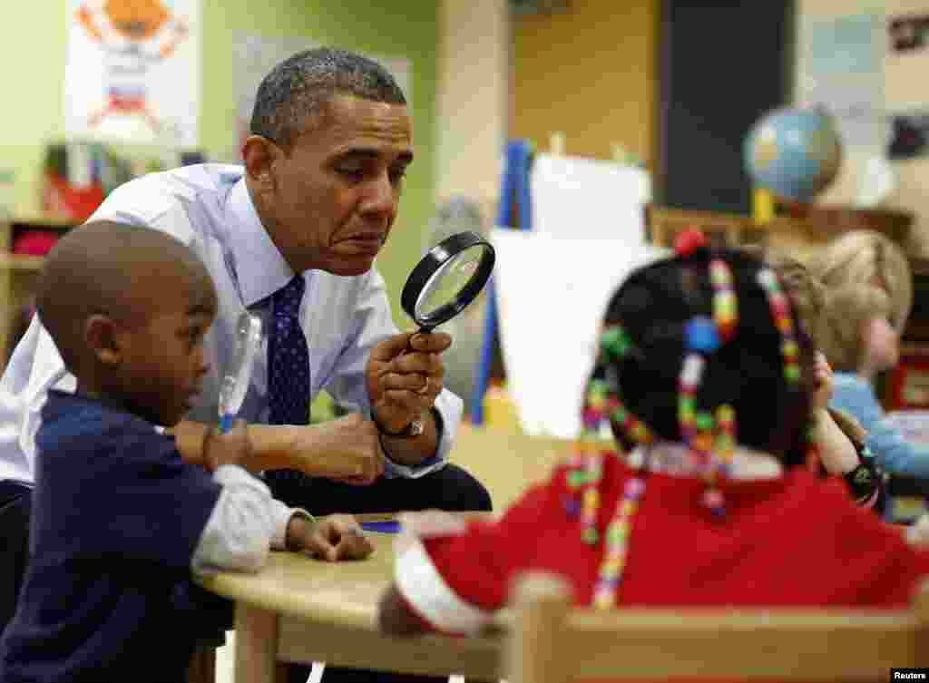 U.S. President Barack Obama uses a magnifying glass to play a game with children in a pre-kindergarten classroom at an early childhood learning center in Decatur, Georgia. (Reuters/Jason Reed)