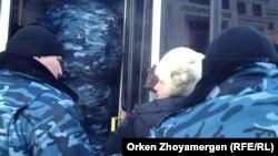 """Полицейские задерживают женщину, пришедшую вместе с другими жильцами комплекса """"Махаббат"""" к зданию генеральной прокуратуры. Астана, 18 декабря 2013 года."""