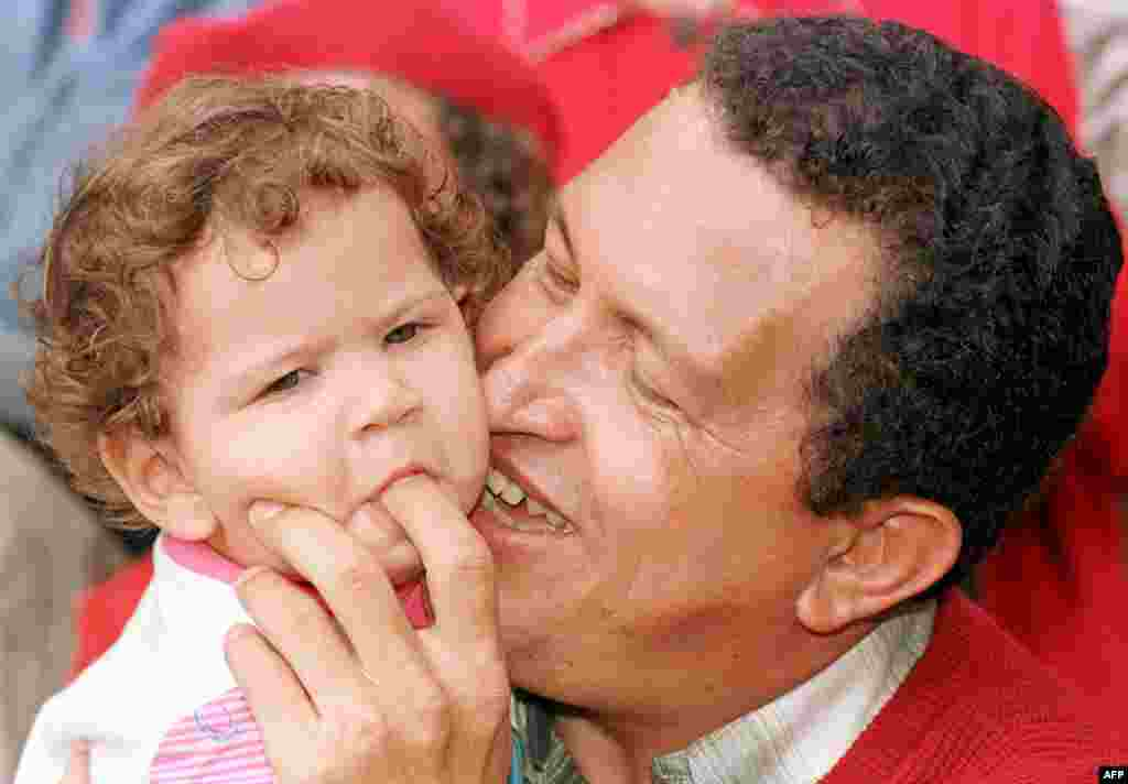 Chavez plays with his 1-year-old daughter Rosa in October 1998.