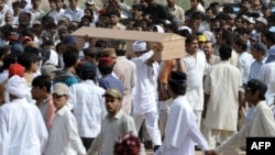 Ahmadi community members carry the coffin of a victim of an attack by gunmen wearing suicide vests on two Ahmadi mosques, during a funeral ceremony in Rabwah in May 2010