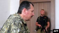 "Self-proclaimed defense minister of the pro-Russian separatist ""Donetsk People's Republic"" Igor Strelkov (left) delivers a press conference as a fellow fighter looks on in Donetsk in July."