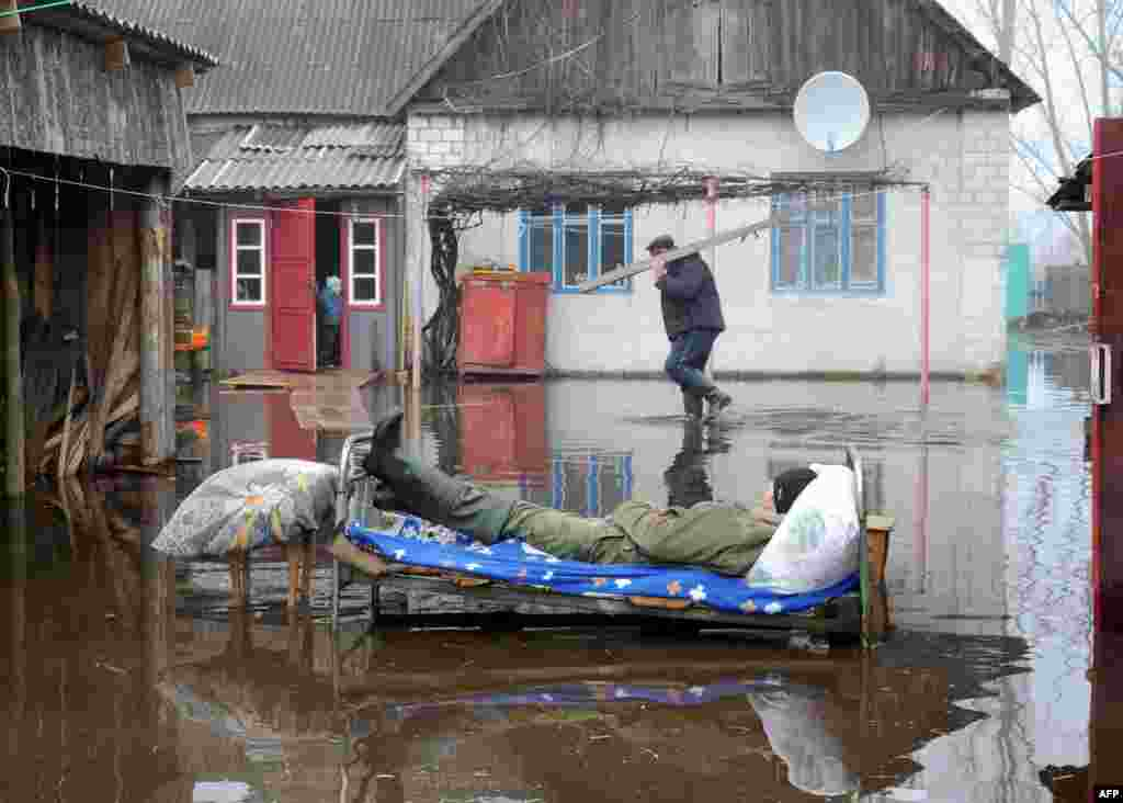 A man rests outdoor during spring floods in the Belarusian village of Khvoensk. (AFP/Viktor Drachev)