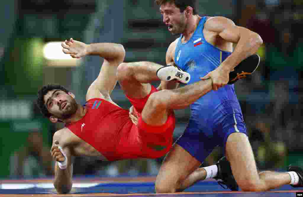 Soslan Ramonov of Russia (in blue) defeated Toghrul Asgarov of Azerbaijan to win the gold medal in the 65-kilogram weight class of men's freestyle wrestling. Uzbekistan's Ikhtiyor Navruzov took bronze.