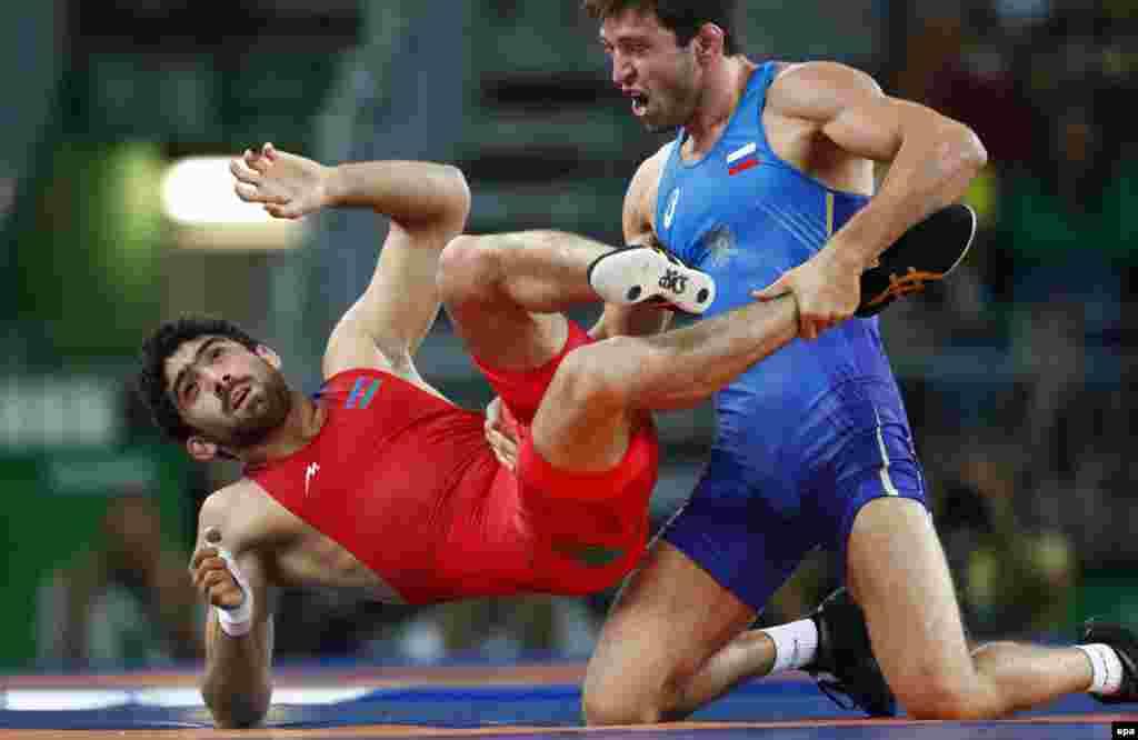 Soslan Ramonov of Russia (in blue) defeated Toghrul Asgarov of Azerbaijan to win the gold medal in the 65-kilogram weight class of men's freestyle wrestling. Uzbekistan's Ikhtiyor Navruzovtook bronze.