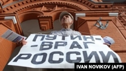 "Vladimir Ionov holds a banner reading ""Putin -- Enemy of Russia"" during a demonstration in Moscow in July, 2013."
