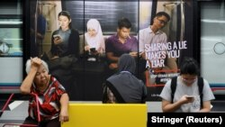 Реклама із закликом не поширювати фейкових повідомлень, вокзал у Куала-Лумпурі, Малайзія, 28 березня 2018 року