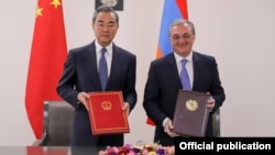 Armenia -- Foreign Ministers Zohrab Mnatsakanian (R) of Armenia and Wang Yi of China sign a visa waiver agreement in Yerevan, May 26, 2019.