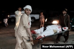 Men carry a wounded man outside a hospital following a car bombing outside a sports stadium in Lashkar Gah on March 23. Thirteen people were killed.