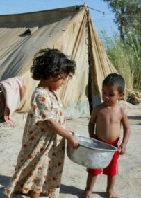 Children carrying water at a displaced-persons camp near Baghdad (epa file photo)