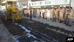 Pakistani paramilitary soldiers watch as a steamroller destroys weapons seized during various search operations against criminal gangs and banned organizations in Karachi on January 6.