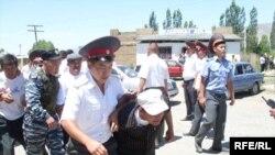 Таласта көчө акциясына чыккан оппозициялык кыймылдын мүчөсүн милиция кызматкерлери кармап, колун толгоп, камаганы алып кетип жатышат. 2009-жыл, 18-июнь.