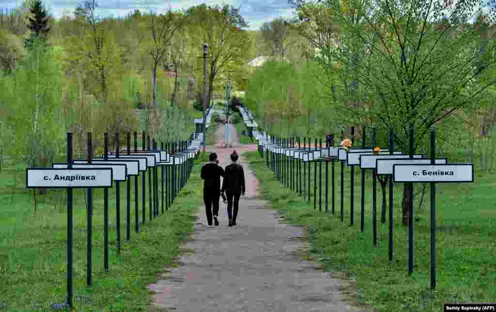 A couple of tourists in Ukraine's exclusion zone walk in a symbolic alley with signs bearing the names of villages and cities that were evacuated following the Chernobyl disaster. (AFP/Sergei Supinsky)