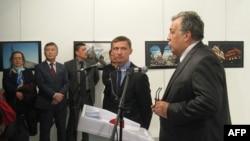 Посол России в Турции Андрей Карлов (справа) выступает на выставке незадолго до того, как будет застрелен нападавшим. Анкара, 19 декабря 2016 года.