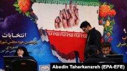Іранці реєструються для участі у виборах. На рекламному зображенні посередині – руки тих, хто проголосував, зі спеціальним чорнилом на пальці, щоб унеможливити повторне голосування