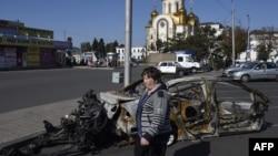 Жанчына праходзіць міма згарэлага аўтамабіля каля чыгуначнай станцыі ў Данецку 15 верасьня