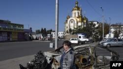 Қала орталығындағы өртенген автокөлік қаңқасы жанынан өтіп бара жатқан әйел. Донецк, 15 қыркүйек 2014 жыл.