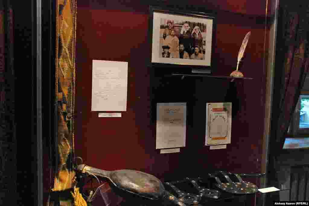 В этой витрине слева внизу — сосуд для кумыса (торсык), принадлежавший Абаю. Справа от него — копия пояса Абая, оригинал хранится в музее в Семее. Эти вещи Абай лично передал историко-этнографическому музею, который открылся в конце XIX века.