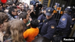 Spanish protestors clash with police a during a 24-hour nationwide general strike in Valencia on November 14.