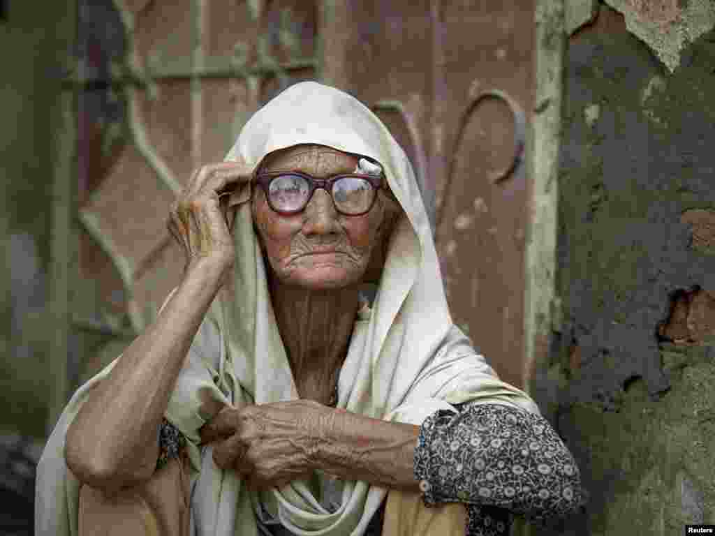 A Pakistani flood victim, 88-year-old Taj Bibi, sits outside her front door awaiting relief supplies, in Charsadda, in Pakistan's northwest Khyber-Pakhtunkhwa Province on August 5. Photo by Akhtar Soomro for Reuters