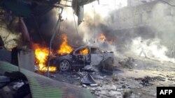 Pamje ku shihet një veturë duke u djegur pas sulmeve të mëparshme në qytetin Darkush në Siri