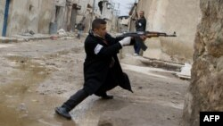 A rebel aims his weapon during clashes with government forces in the streets of Aleppo on March 4.