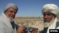 Two Afghan men receive solar-powered radios from Radio Azadi. (09Oct2010)