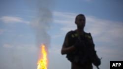 Український військовий стоїть на сторожі, а позаду горить газопровід, який був пошкоджений в результаті обстрілу сепаратистами поблизу Авдіївки, що на Донеччині, 12 червня 2015 року
