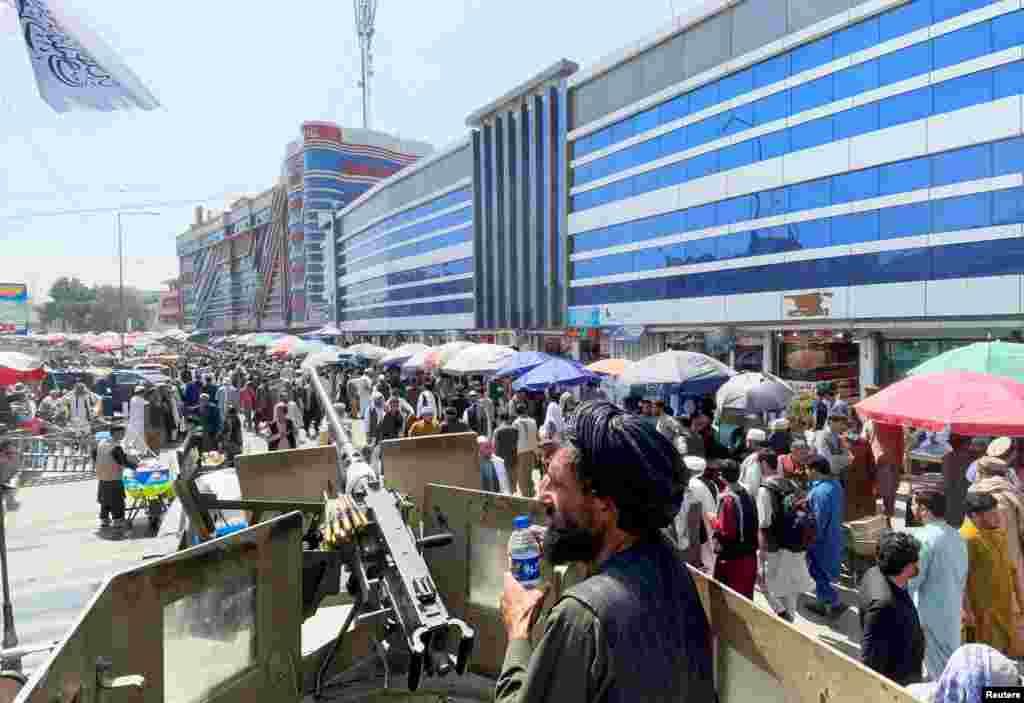 Membri ai forțelor de securitate talibane asigură securitatea, în timp ce mulțimile de oameni trec pe lângă o piață de schimb valutar din Kabul, 4 septembrie 2021. După preluarea conducerii Afganistanului de către talibani, băncile, instituțiile guvernamentale, școlile și universitățile s-au închis în mare parte a țării.