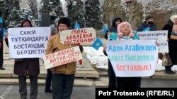 Люди с плакатами, с призывами освободить политических заключенных и не допустить передачи земли в аренду иностранцам, на митинге в Алматы. 14 ноября 2020 года.