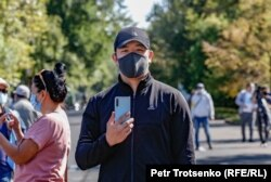 Мужчина в защитной маске с телефоном в руках на санкционированном властями митинге. Алматы, 13 сентября 2020 года.