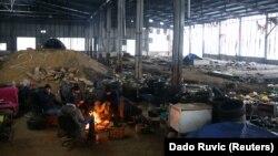 Boszniában, Velika Kladusa mellett, egy elhagyott gyárépületben próbálnak migránsok melegedni 2021. január 31-én.