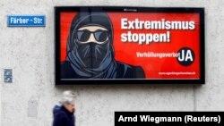 """Бурка киіп жүруге қарсы науқан аясында ілінген постерде """"Экстремизмді тоқтат!"""" деп жазылған."""