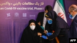 A woman receives an injection during the first trial phase of a locally made Iranian vaccine for COVID-19 in Tehran on December 29.